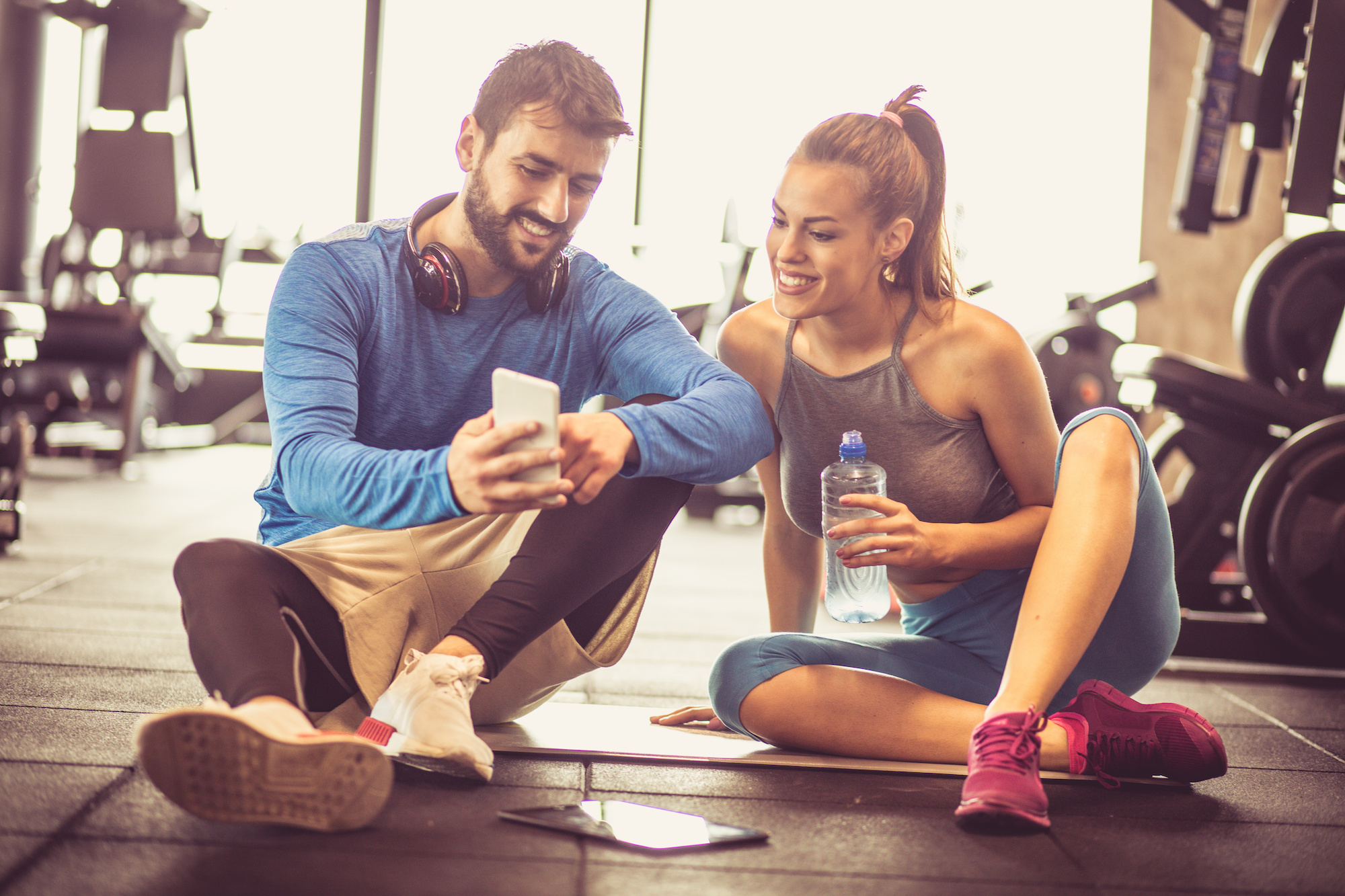 Personal trainer with young sports girl sitting on floor and having conversation after exercise. Using mobile phone.